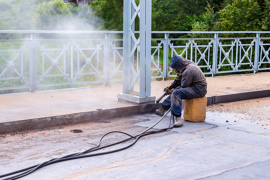 Worker with protective mask while doing a mobile sand blasting