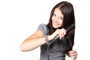Woman straightening her hair with a hair iron