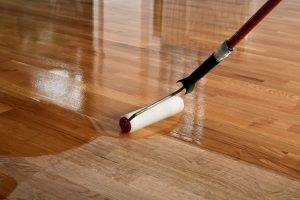 Worker lacquering timber floor