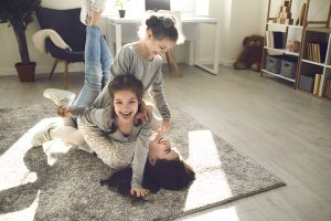 Happy mother and cute little children playing in a warm modern rug